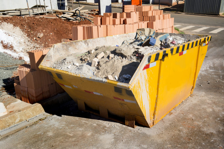 Photo of a yellow concrete dumpster at a construction site.